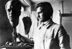 """Das Foto zeigt Wilhelm Lehmbruck 1918 in seinem Züricher Atelier vor der Skulptur """"Portraitkopf Fritz von Unruh""""."""