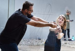 Das Foto zeigt einen Mann und eine Frau, die zusammen eine Glasscheibe von beiden Seiten bemalen.