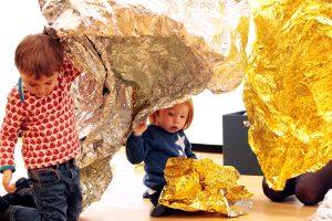Das Foto zeigt zwei Kinder, die mit einer Goldfolie spielen.