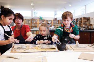 Das Foto zeigt eine Kunstvermittlerin, die mit drei Kindern im Atelier kreativ arbeitet.