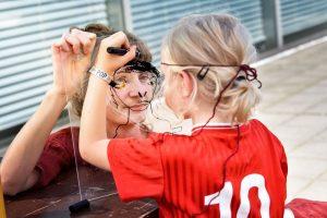 Das Foto zeigt zwei Kinder, die sich gegenseitig durch eine Glasscheibe porträtieren.