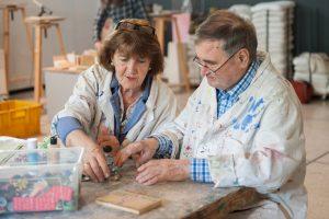 Das Foto zeigt einen Mann mit Demenz und eine Begleiterin, die zusammen kreativ arbeiten.