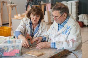 Das Foto zeigt zwei Menschen mit Demenz bei kreativer Arbeit im Atelier.