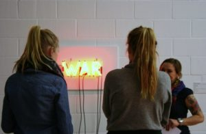 """Das Foto zeigt zwei Schülerinnen, die vor Bruce Naumans Werk """"Raw War"""" stehen."""