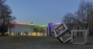 """Das Bild zeigt eine Außenansicht des Lehmbruck Museums, das durch das Werk """"Lightline"""" von Waltraud Cooper durch Regenbogenfarben-LEDs leuchtet."""