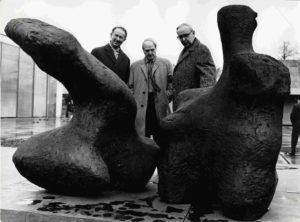 """Das Schwarz-Weiß-Foto zeigt den Künstler Henry Moore zwischen Oberbürgermeister August Seeling (links) und Museumsdirektor Gerhard Händler am 25. März 1965 auf dem Skulpturenhof des Lehmbruck Museums. Sie stehen hinter der Skulptur """"Two Piece Reclining Figure No. 1"""", die Henry Moore 1959 schuf."""