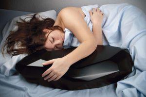 """Das Foto zeigt das Werk """"Robot"""" von Susanna Hertrich. Eine schlafende Frau umarmt ein künstlich wirkendes Objekt."""