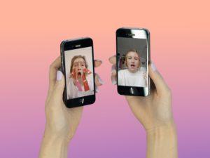 """Das Foto ist ein Werk von Duo Mobiel: """"Free the Expression"""". Es zeigt zwei Hände, die Handys halten. Auf den Bildschirmen sind Porträts zu sehen."""
